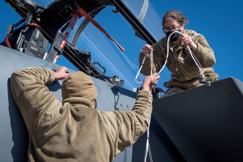 Airman 1st Class Quentin Thompson (left) and Senior Airman Kierra Hamil (right), 4th Component Maintenance Squadron electrical and environmental technicians, pass a testing harness at Seymour Johnson Air Force Base, North Carolina, Feb. 3, 2021.