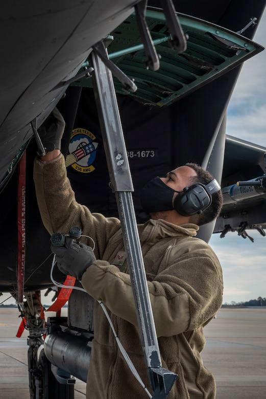 Senior Airman Thiago Santos, 4th Fighter Readiness Squadron electronics technician, attaches a test harness onto an F-15E Strike Eagle at Seymour Johnson Air Force Base, North Carolina, Feb. 3, 2021.