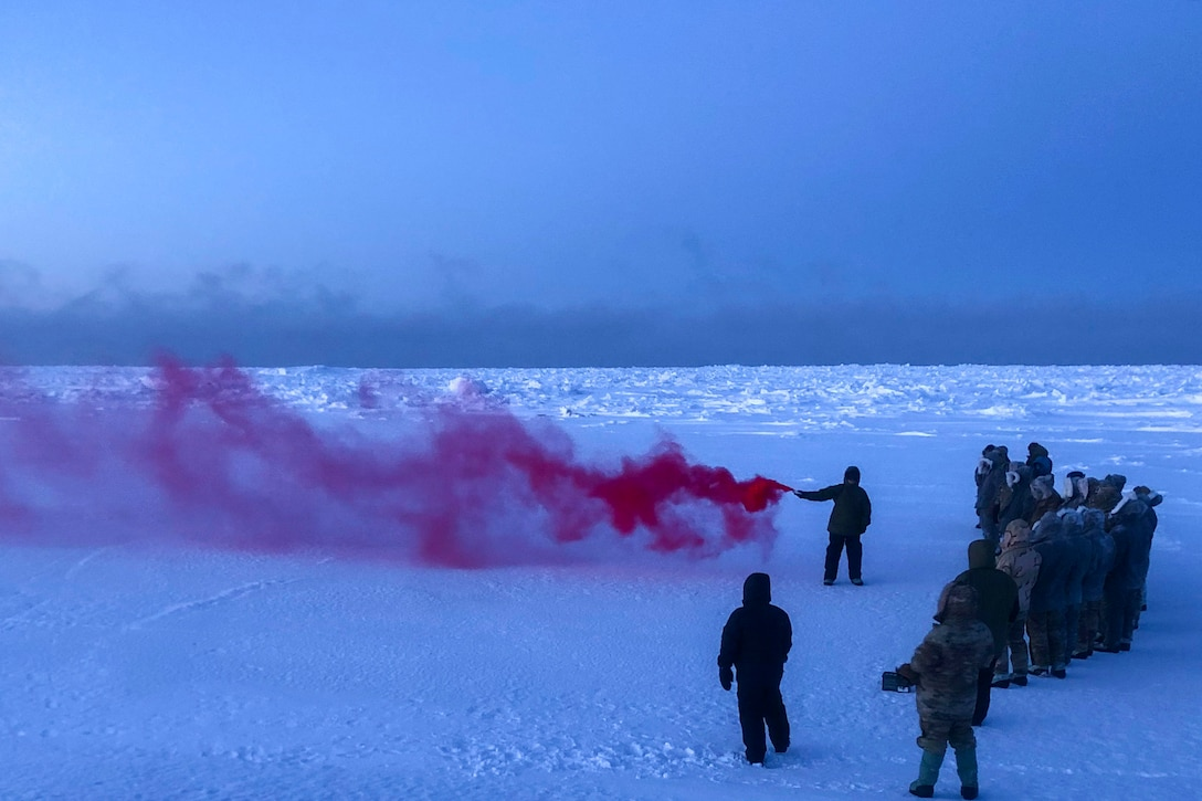 Service members watch as a streak of red smoke appears from an airman using a flare.