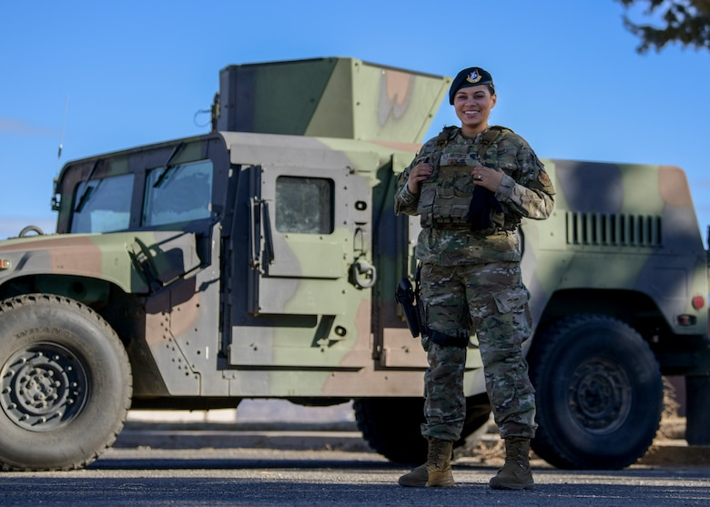 Woman stands and poses in front of humvee