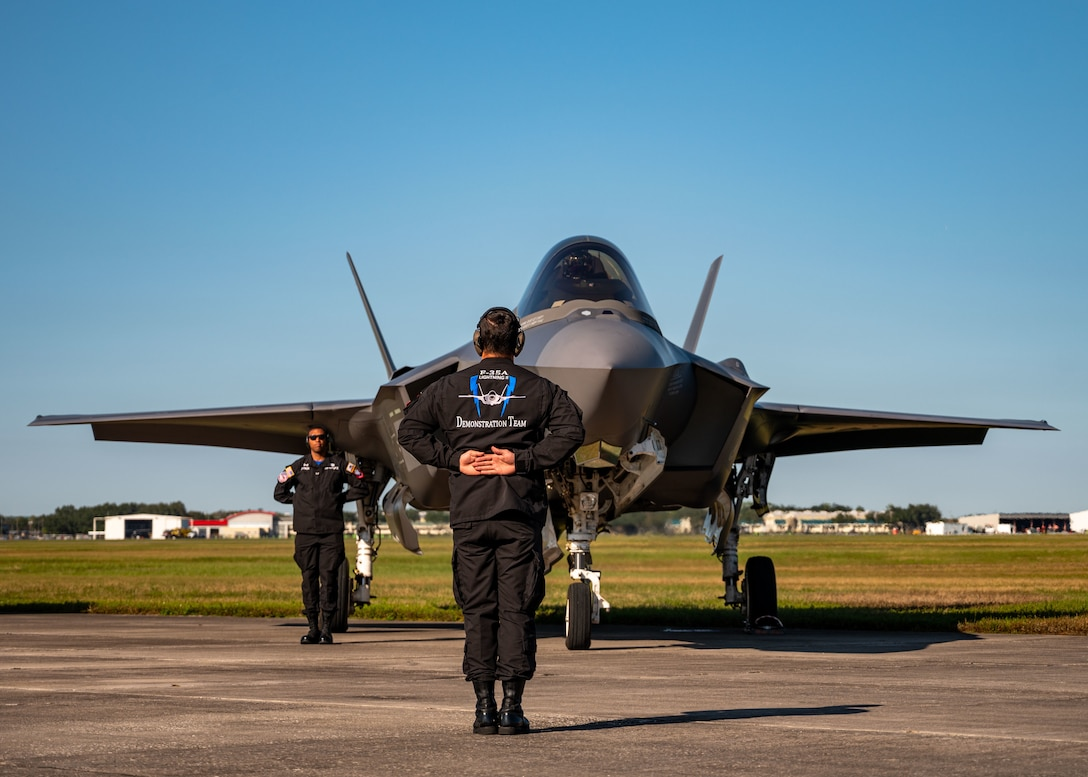 Two Airmen stand next to an F-35 fighter jet.
