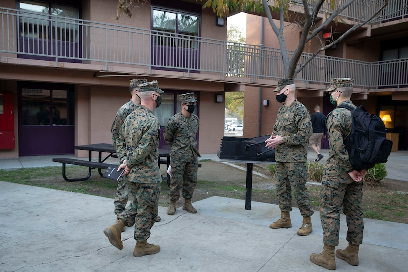 A group of Marines stands talking in front base housing.