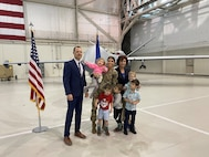 Maj. Jennifer stands with her family in front of an MQ-9 Reaper for a photo.