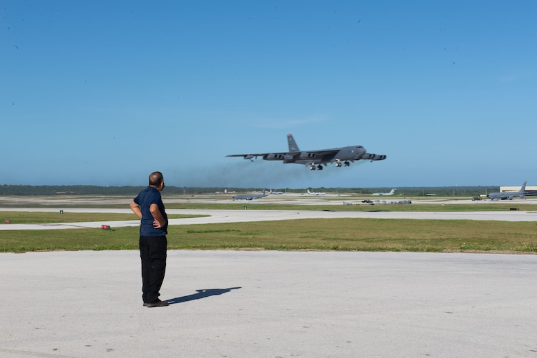 Raymon Perez, 736th Security Forces Squadron, watches a B-52 Stratofortress take off from Andersen Air Force Base, Guam, Feb. 10, 2021.