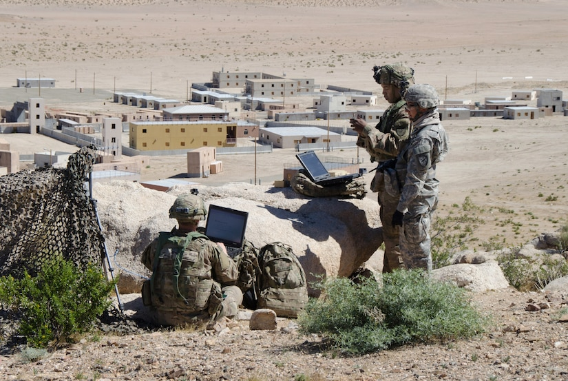 Soldiers of 780th Military Intelligence Brigade set up cyber tools overlooking mock city of Razish at National Training Center, Fort Irwin, California, May 7, 2017 (U.S. Army/Bill Roche)