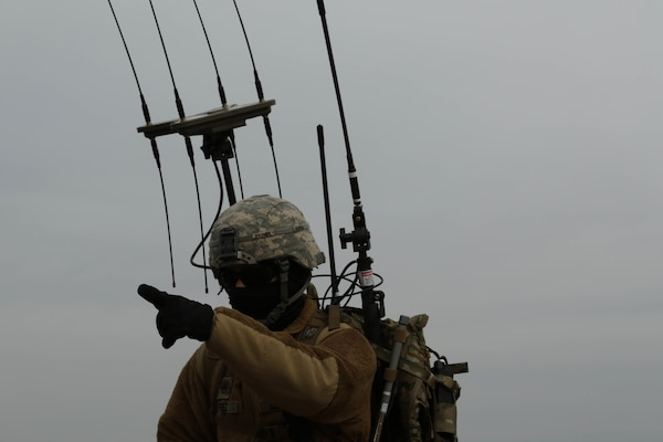 Soldier with Cyber Electromagnetic Activities section, 1st Armored Brigade Combat Team, 1st Infantry Division, points toward nearby objective during final day of training with section's new electronic warfare equipment, Fort Riley, Kansas, April 6, 2018 (U.S. Army/Michael C. Roach)