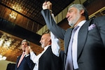Former Secretary of State John Kerry raises hands with Afghan presidential candidates Ashraf Ghani, left, and Abdullah Abdullah, right, at United Nations Mission Headquarters in Kabul, on July 12, 2014, after announcing deal to settle election dispute (U.S. Department of State)