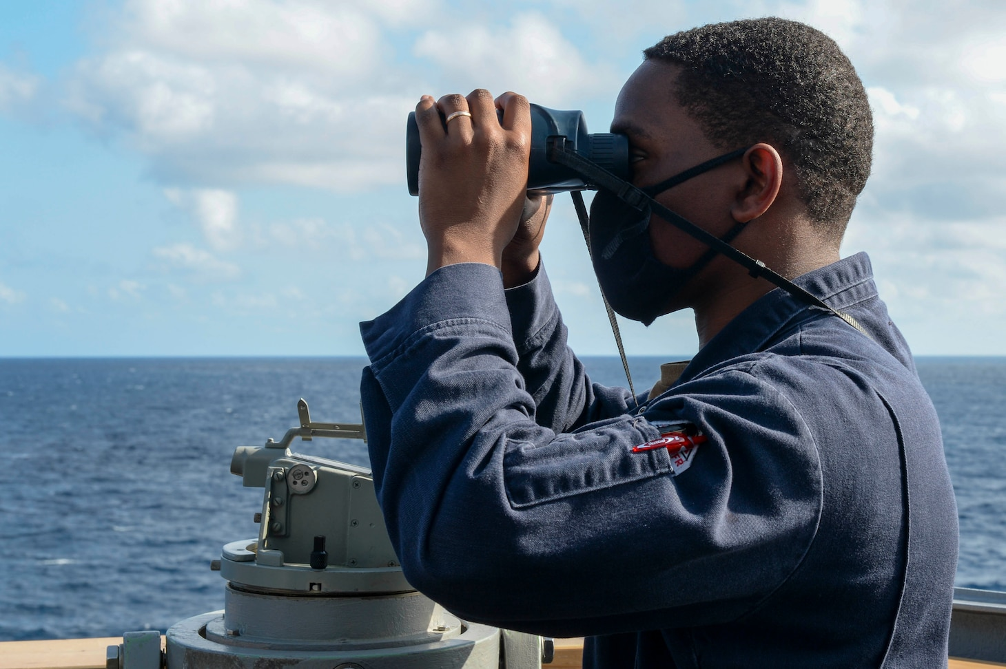 U.S. Navy Ensign Ryan Simpson, from Baltimore, looks through a pair of binoculars on the bridge wing as the guided-missile destroyer USS Russell (DDG 59) conducts routine underway operations.
