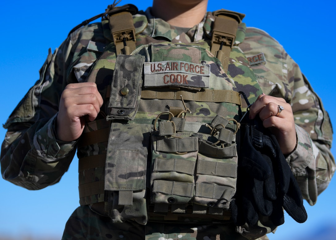 Senior Airman Kiah C. Cook, 377th Security Forces Group defender, donns her body armor at Kirtland Air Force Base, N.M., Feb. 4, 2021. Airmen from the 377th SFG were among the first Air Force defenders to receive the new issue of female body armor starting January 2021.