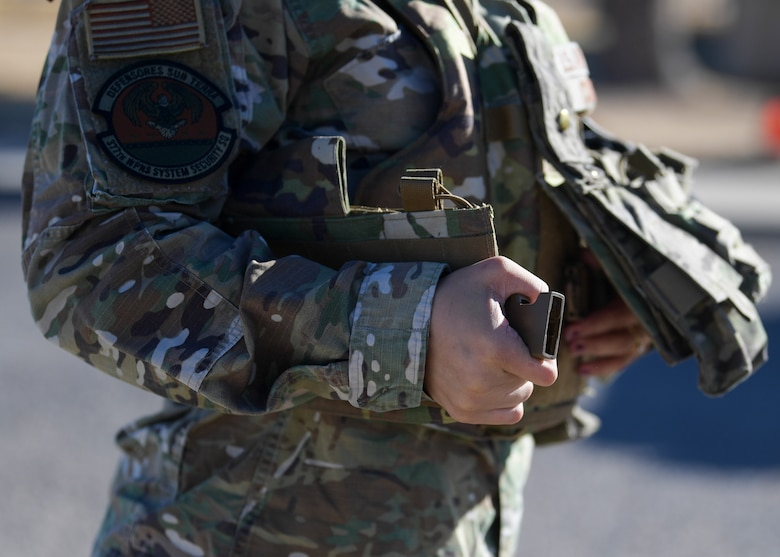 Senior Airman Kiah C. Cook, 377th Security Forces Group defender, donns her body armor at Kirtland Air Force Base, N.M., Feb. 4, 2021. One of the features on the new female body armor is a snap buckle instead of the original velcro, which is used on the standard vest. The adjustable back corset allows the wearer to tighten the fit, making it more secure.
