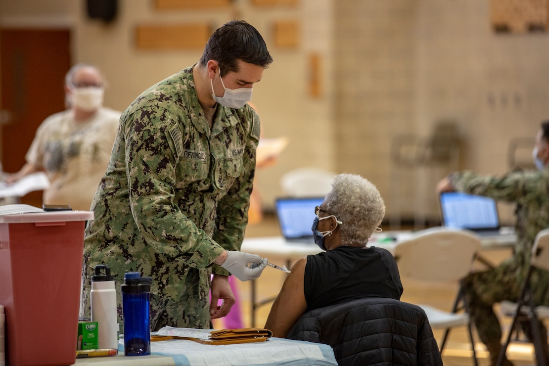 U.S. Navy Hn. David D. Pettingill, left, a corpsman with Naval Medical Center Camp Lejeune (NMCCL), administers the COVID-19 vaccine on Marine Corps Base Camp Lejeune, North Carolina, Feb. 16, 2021 while supporting  a mass COVID-19 vaccination center set up for Marine Corps Installations East personnel and beneficiaries. Beginning Feb. 16, 2021, NMCCL personnel will be able to provide vaccinations for any eligible personnel with the capability of vaccinating up to 2000 people per day. (U.S. Marine Corps Photo by Lance Cpl. Isaiah Gomez)