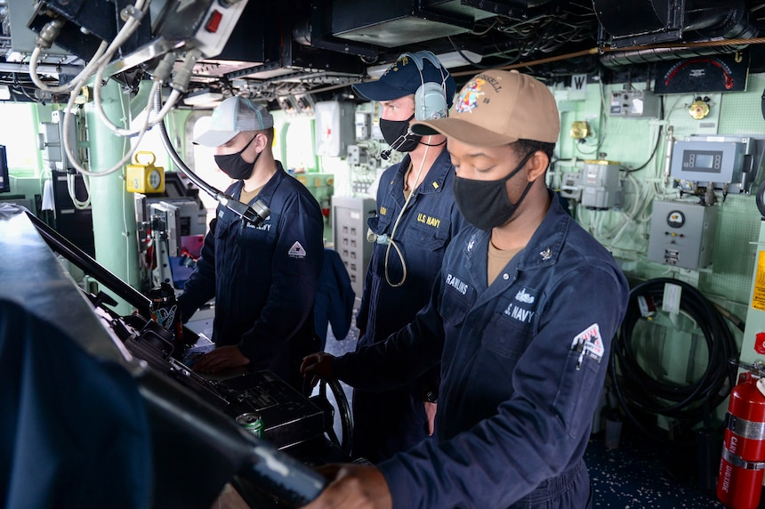 U.S. Sailors stand watch at the helm on the bridge as the guided-missile destroyer USS Russell (DDG 59) conducts routine underway operations.
