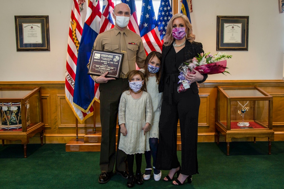 U.S. Marine Corps Staff Sgt. Justin A. Collins, a motor vehicle operator with Combat Logistics Battalion 8, Combat Logistics Regiment 2, 2nd Marine Logistics Group, poses for a photo with his family following a recognition ceremony in his honor as the 2020 Service Member of the Year at building 1 on Marine Corps Base Camp Lejeune, North Carolina, Feb. 8, 2021. The Jacksonville-Onslow Chamber of Commerce, Military Affairs Committee, recognized Collins for his outstanding performance and dedication. (U.S. Marine Corps photo by Cpl. Karina Lopezmata)
