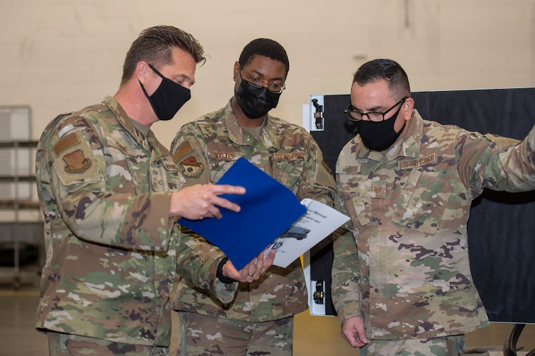 From left, U.S. Air Force Senior Master Sgt. Robert Cliché, flight chief of the 116th Aerospace Ground Equipment (AGE) Flight, Georgia Air National Guard, shows a new ground power unit (GPU) operation manual to Tech. Sgt. Anthony Walker, AGE familiarization instructor, and Tech. Sgt. Juan Felix, AGE production superintendent, both with the active duty 461st AGE Flight, Robins Air Force Base, Georgia, Jan. 21, 2021. Squadron Innovative Funding used to obtain the new specialized aircraft generators was the first step in Team JSTARS replacing the aging GPUs.(U.S. Air National Guard photo by Master Sgt. Nancy Goldberger)
