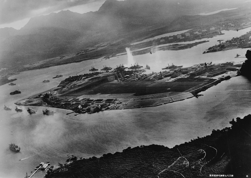 Photograph taken from Japanese plane during torpedo attack on ships moored on both sides of Ford Island; view looks about east, with supply depot, submarine base, and fuel tank farm in right center distance; torpedo has just hit USS West Virginia on far side of Ford Island (center); other battleships moored nearby are (from left): USS Nevada, USS Arizona, USS Tennessee (inboard of West Virginia), USS Oklahoma (torpedoed and
