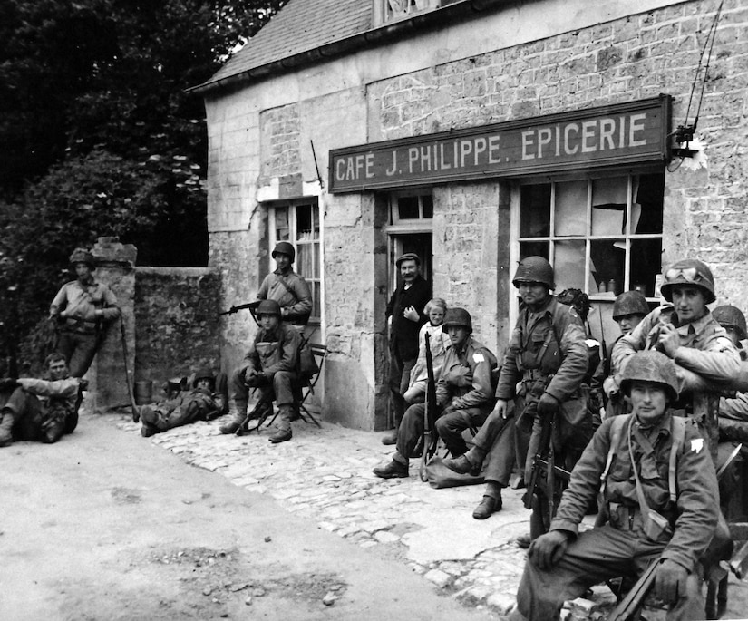 Soldiers relax outside French café, in Sainte-Mère-Eglise, France, June 6, 1944 (National Archives and Records Administration/National Museum of the U.S. Navy)