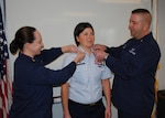 MICHIGAN CITY, Ind. - Senior Chief Petty Officer Colleen McCarthy, (left), officer-in-charge of Coast Guard Station Kenosha, Wis., and Senior Chief Petty Officer Michael Beatty, officer-in-charge of Coast Guard Station Frankfort, Mich., pin new rank insignias on the collar of Rebecca Polzin, officer-in-charge of Coast Guard Station Michigan City during her advancement to senior chief petty officer, Feb. 2, 2012. As officer-in-charge, Polzin ensures the 19 enlisted active duty members and 7 enlisted Coast Guard reservists at Station Michigan City carry out their missions of search and rescue; maritime law enforcement; ports, waterways, and coastal security; and marine environmental protection. U.S. Coast Guard photo by Seaman Kody Felthoff.