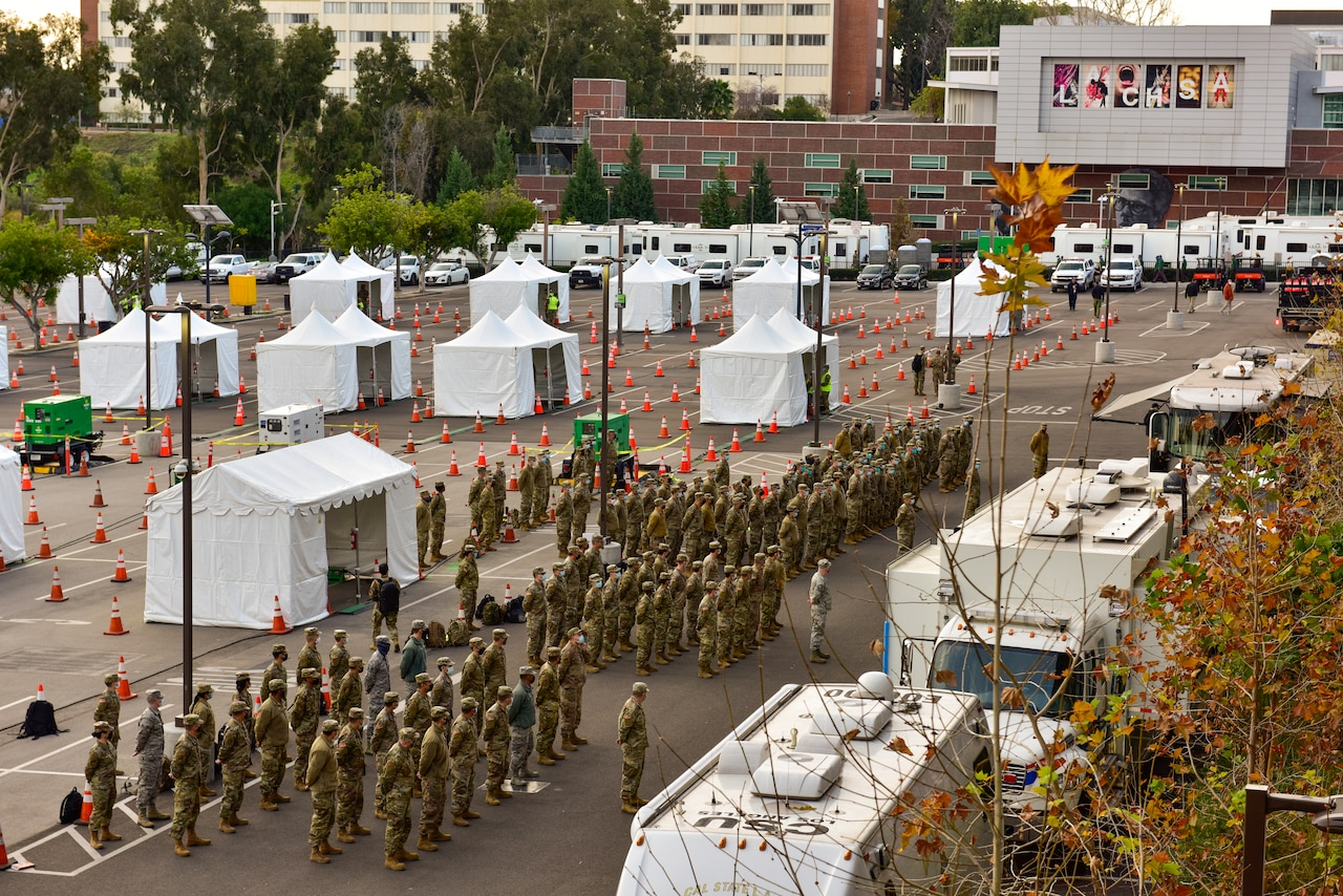 Dozens of service members stand in formation in a parking lot near an array of white tents.
