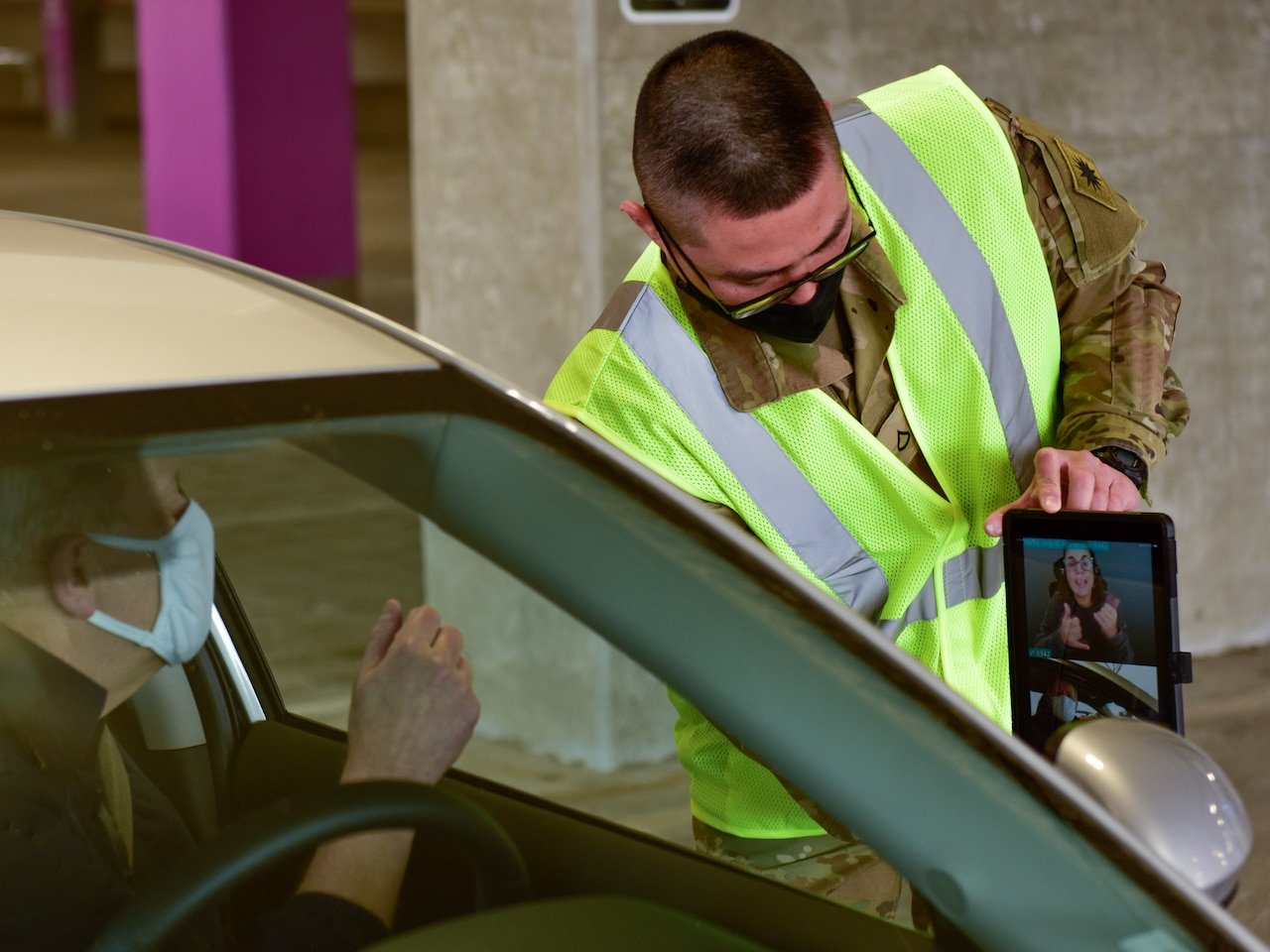 A man in a military uniform holds a computer tablet and shows it to a man in the driver's seat of an automobile.