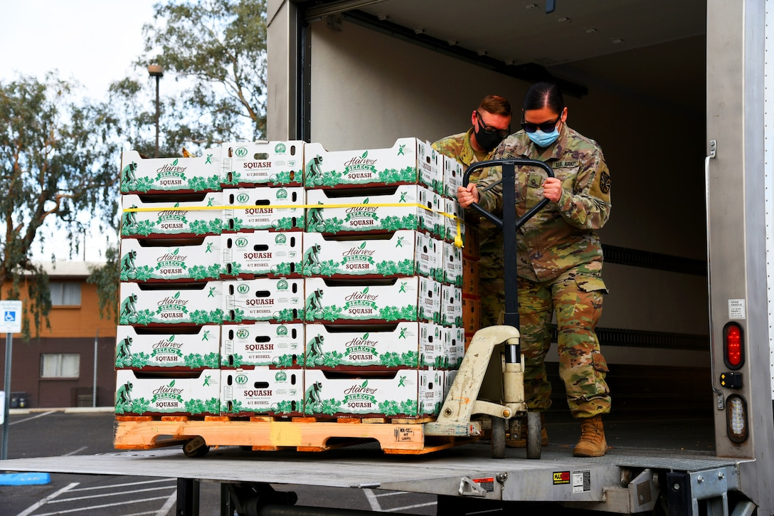 Two soldiers wearing  face masks help unload boxes of produce for distribution.