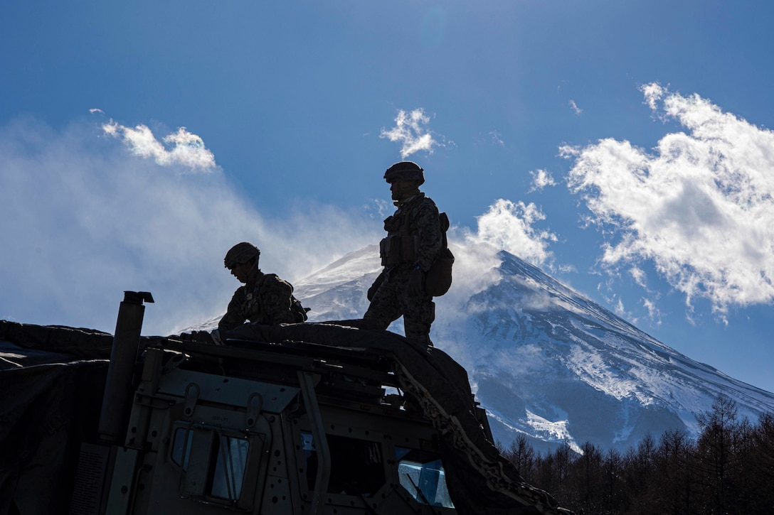 Two Marines shown in silhouette set up military equipment in front of a mountain.