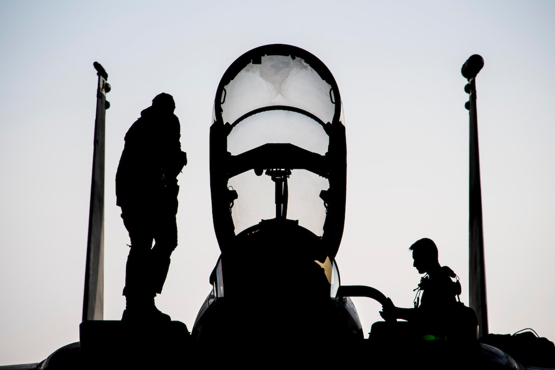 Two airmen shown in silhouette stand on an aircraft.