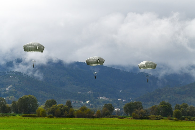 Three paratroopers descend toward a field.