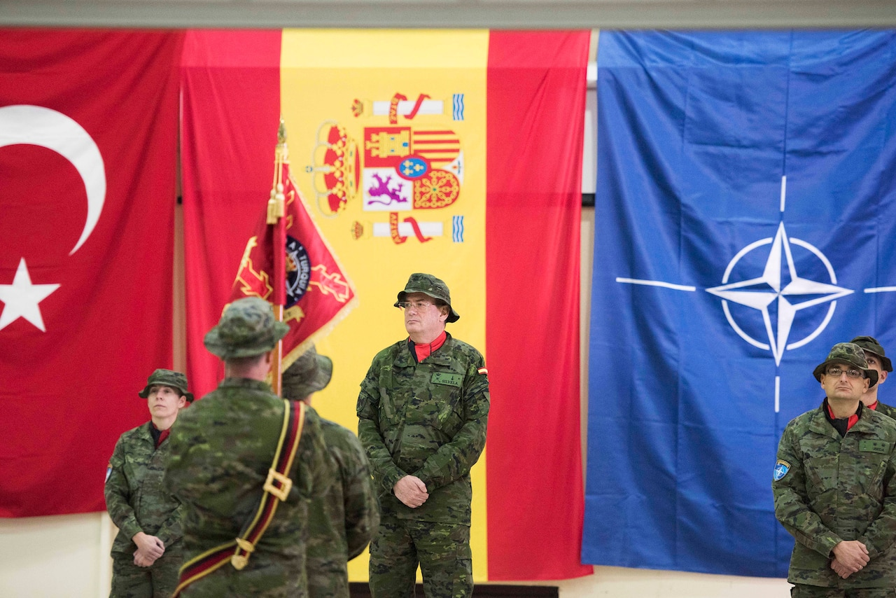 Five soldiers stand in front of flags.