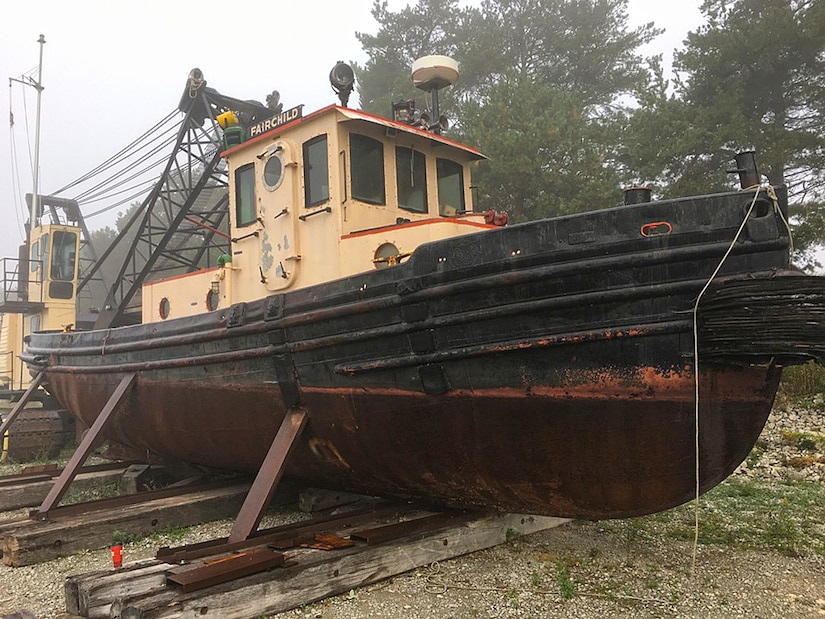 A tugboat in dry storage on a beach.