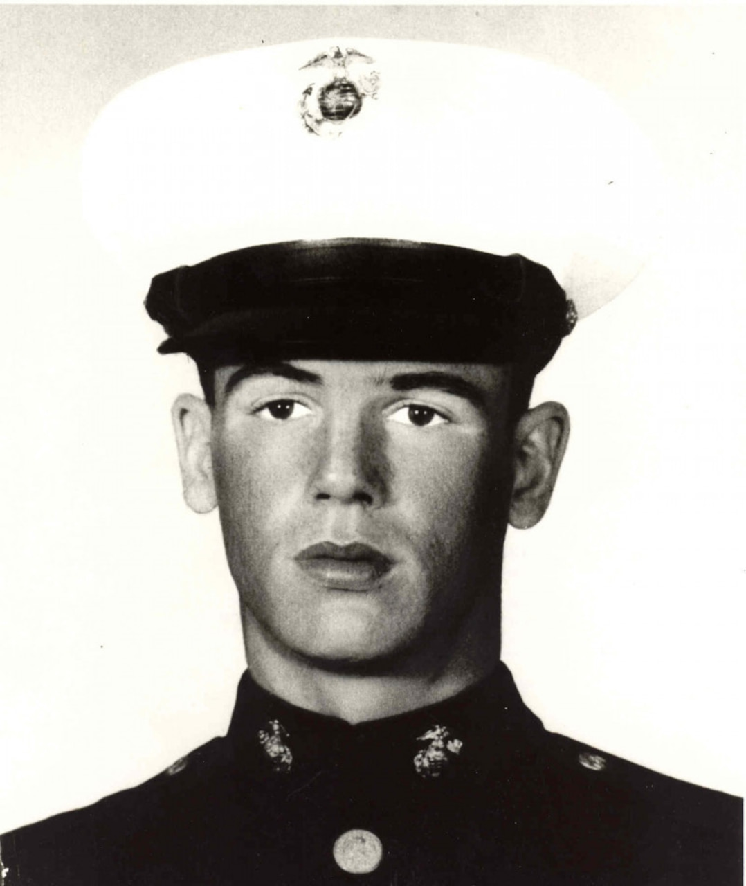 A man in uniform and a dress cap looks straight ahead.