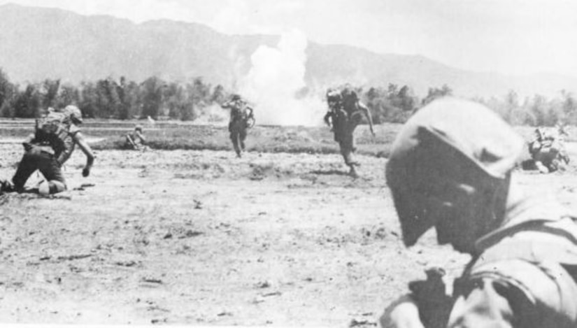 Men in combat gear run through an open field toward an explosion.