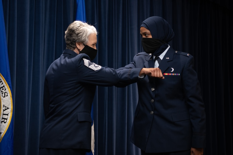 Chief Master Sgt. Natalie Gray, Air Force Chaplain Corps senior enlisted advisor and religious affairs career field manager, congratulates Chaplain 1st Lt. Saleha Jabeen, a graduate of Basic Chaplain Course Class 21A, with an elbow bump Feb. 5, 2021, at the Ira C. Eaker Center for Leadership Development on Maxwell Air Force Base, Ala. Gray attended the graduation with Maj. Gen. Steven Schaik, Air Force chief of chaplains, to celebrate the graduates' accomplishment in a modified ceremony to adhere to guidance from the Centers for Disease Control and Prevention and the Department of Defense.