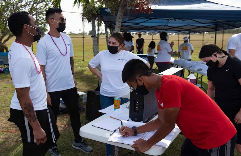 Volunteers help sign people in for the first ever Fat Tuesday 5K fun run at Andersen Air Force Base, Guam, Feb. 16, 2021.