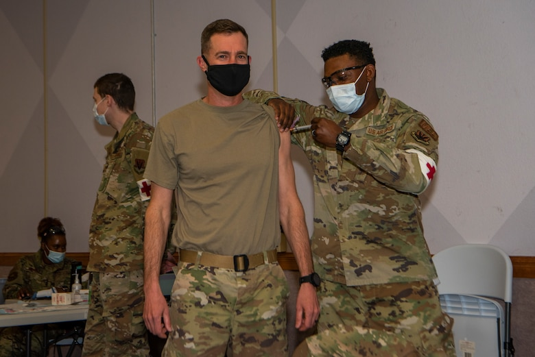 Airman standing receiving a vaccine