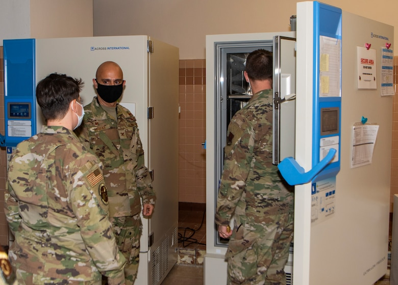 three airmen looking into a freezer