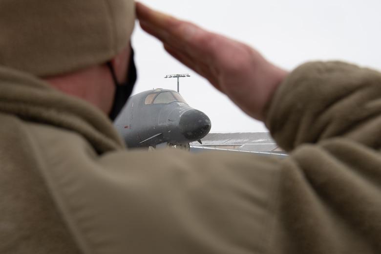 Master Sgt. David Jackson, the 28th Aircraft Maintenance Squadron production superintendent, renders a farewell salute a B-1B Lancer being divested prior to its final departure from Ellsworth Air Force Base, S.D., Feb. 17, 2021. This limited aircraft divestiture will contribute to funding investments in key capabilities for the future bomber force and allow B-1B maintainers to focus their efforts on the healthiest B-1s that remain in the fleet.  (U.S.  Air Force photo by Airman Jonah Fronk)