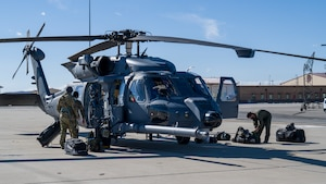 """Crews off-load from two HH-60W """"Jolly Green II"""" combat rescue helicopters at Edwards Air Force Base, California, Feb. 17. The HH-60Ws arrived from Eglin AFB, Florida, to conduct flight test operations. (Air Force photo by Giancarlo Casem)"""