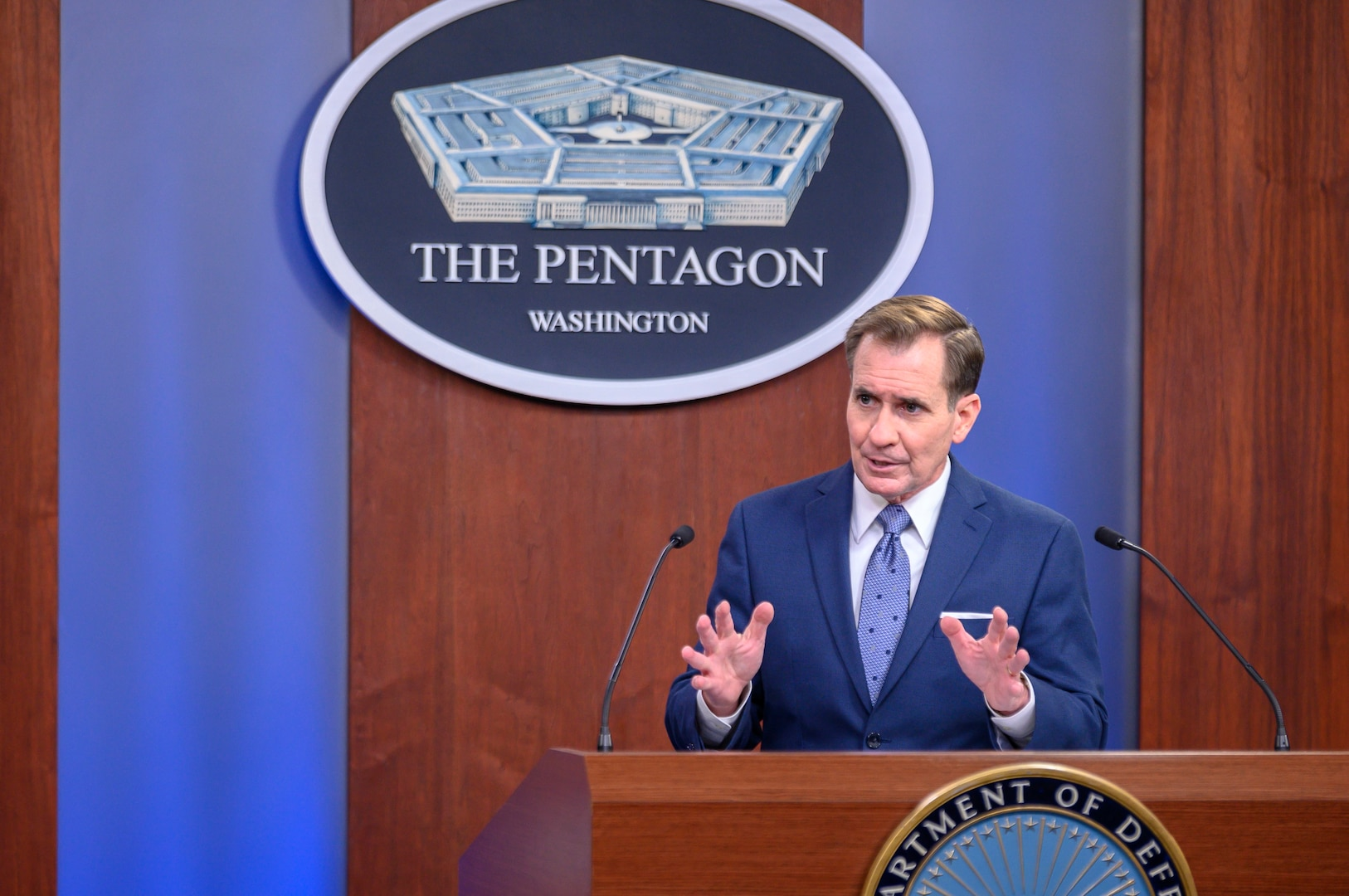 A man at a lectern with two microphones gestures. The sign behind him indicates that he is at the Pentagon.