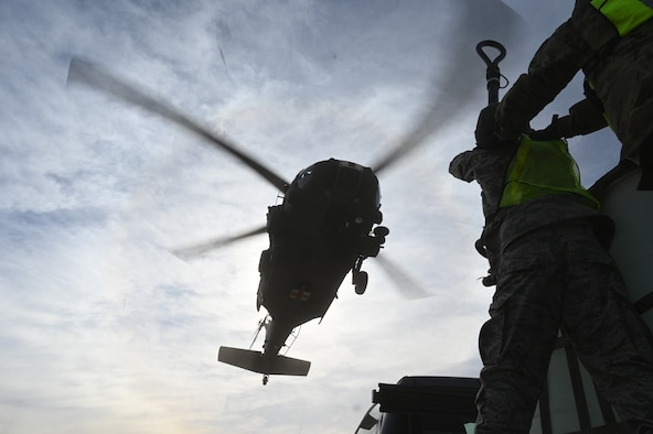 Tech. Sgt.  Brasil A. Segura (right), 352nd Recruiting Squadron in-service Air Force Reserve recruiter, braces Senior Airman Arturo Delgado, 26th Aerial Transportation Squadron aerial porter, as they prepare to attach a 2,000 pound A-22 cargo bag to a UH-60 Black Hawk helicopter flown by Texas Army National Guard Soldiers.