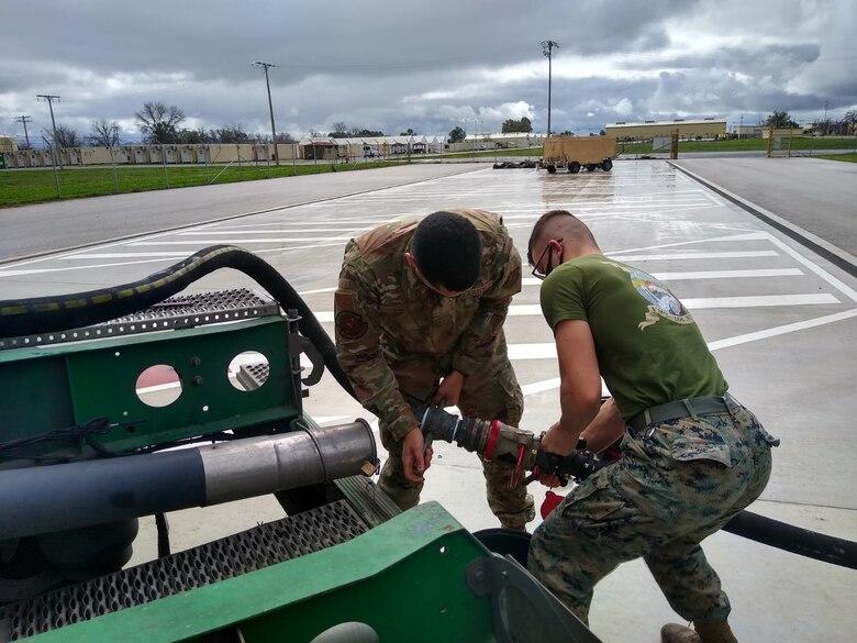 U.S. Air Force Senior Airman Josué Ayala Pérez, 496th Air Base Squadron fuels technician, assists a U.S. Marine with a fuel pump at Morón Air Base, Spain