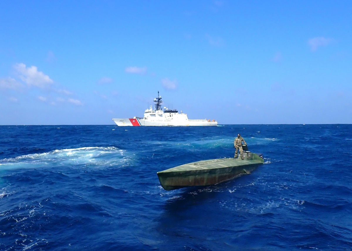 A Coast Guard Cutter Bertholf (WMSL 750) boarding team member stands atop an interdicted low-profile vessel in the Eastern Pacific Ocean, Feb. 1, 2021.