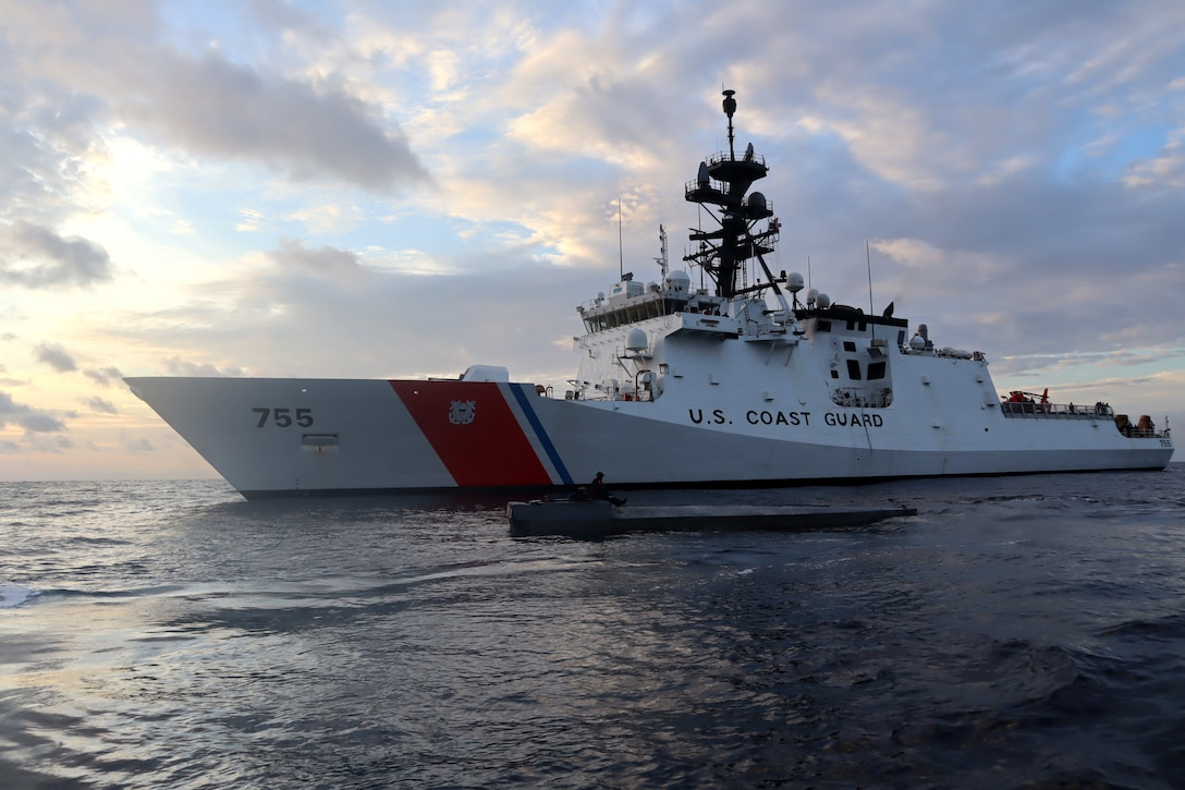 Coast Guard Cutter Munro (WMSL 755) boarding team member sits atop an interdicted low-profile vessel in the Eastern Pacific Ocean after crews seized 3,439 pounds of cocaine from the LPV, Jan. 27, 2021.