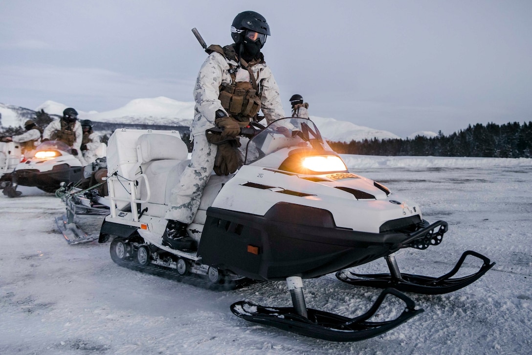 A Marine operates a snowmobile; others are seen behind.
