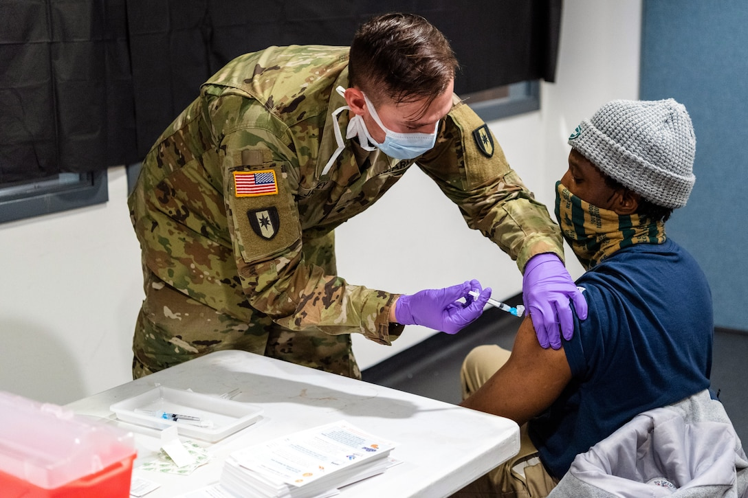 A soldier wearing a face mask and gloves leans down to give an injection to a man who's wearing a face mask seated in a chair.