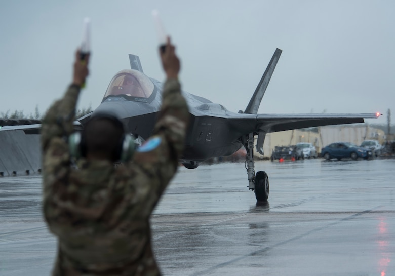 An Airman from the 356th Aircraft Maintenance Unit at Eielson, Air Force Base, Alaska, marshalls an F-35A Lightning II, also from Eielson AFB as part of Cope North 21 at Andersen AFB, Guam, Feb. 6, 2021. Approximately 2,200 personnel and 97 aircraft were brought together for Cope North 21 with the mission to improve combat readiness, increase interoperability between U.S. Air Force, Royal Australian Air Force and Japan Air Self-Defense Force, or Koku-Jieitai. (U.S. Air Force photo by Senior Airman Jonathan Valdes Montijo)
