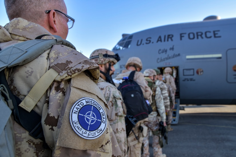 International troops board an Air Force transport plane.