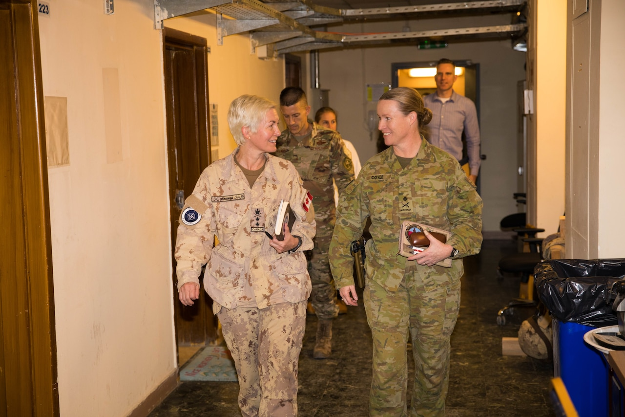 Two general officers walk through a hall.