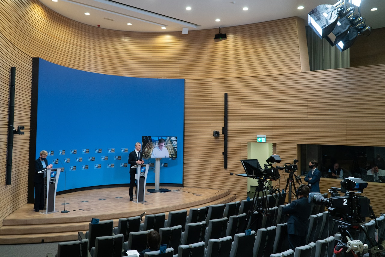 Man in nearly-empty auditorium speaks to TV cameras.