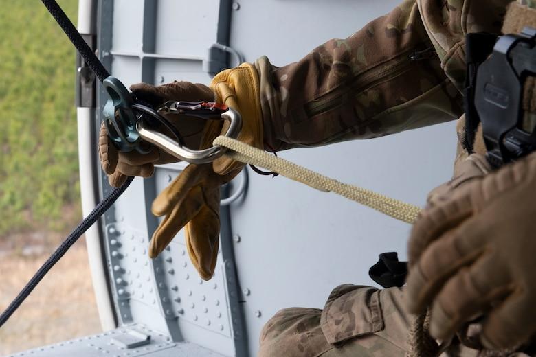 A rescue airman adjusts his rappel line.