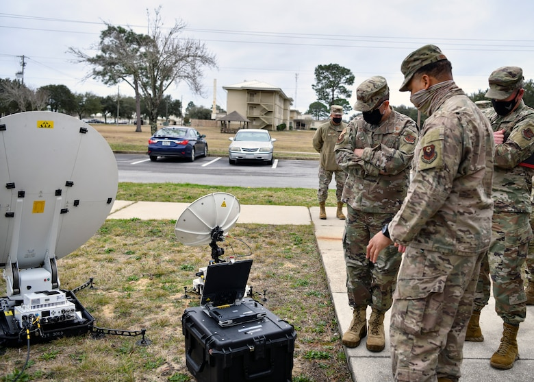 Photo of Airmen looking at satellite dishes